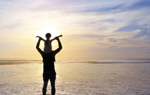 silhouette-father-were-riding-neck-carries-daughter-look-out-at-the-sea-at-sunset_38678-93